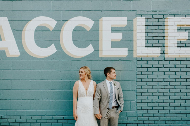 wedding couple against wall at Accelerator Space
